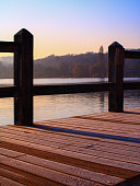 Wooden pontoon with snow at the edge of a lake at sunrise