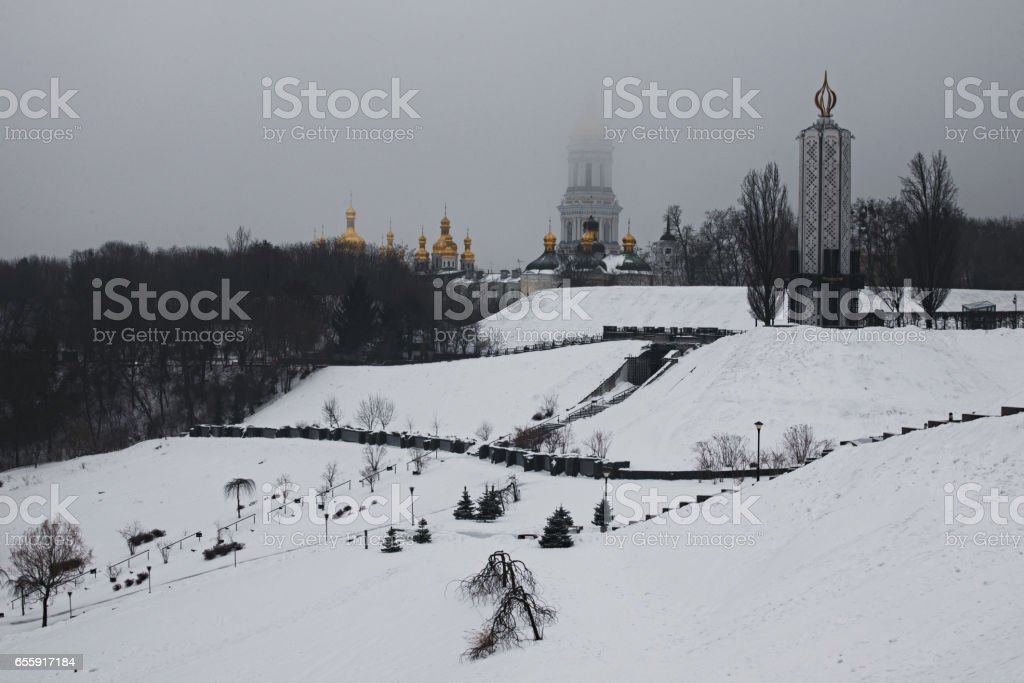 Frosty morning in the park. National Museum 'Memorial to Holodomor victims' and top of Great Lavra Bell Tower is disappearing in the fog. Kiev. Ukraine stock photo