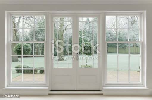 Beautifully crafted Georgian white wooden windows and patio doors with a view towards a wintery garden covered in frost.