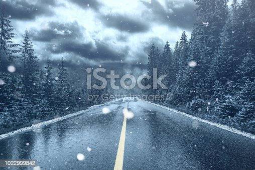 Frosty weather and falling snow on a street. Glacial surface roadway.