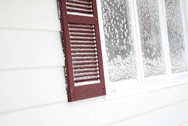 frosty window with brown shutter in the winter stock photo