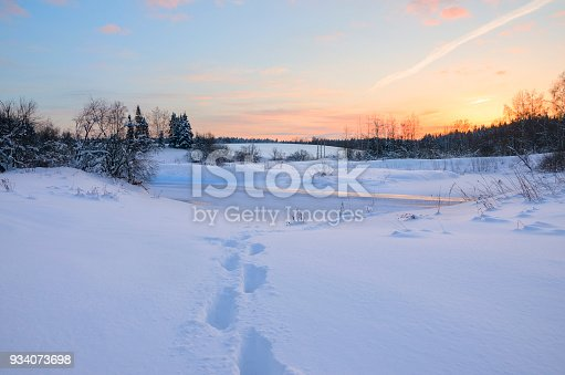 1034754000istockphoto Frosty winter landscape with frozen river.Twilight.Cold morning.Snow covered trees.Sunrise.Footprints in drifts 934073698