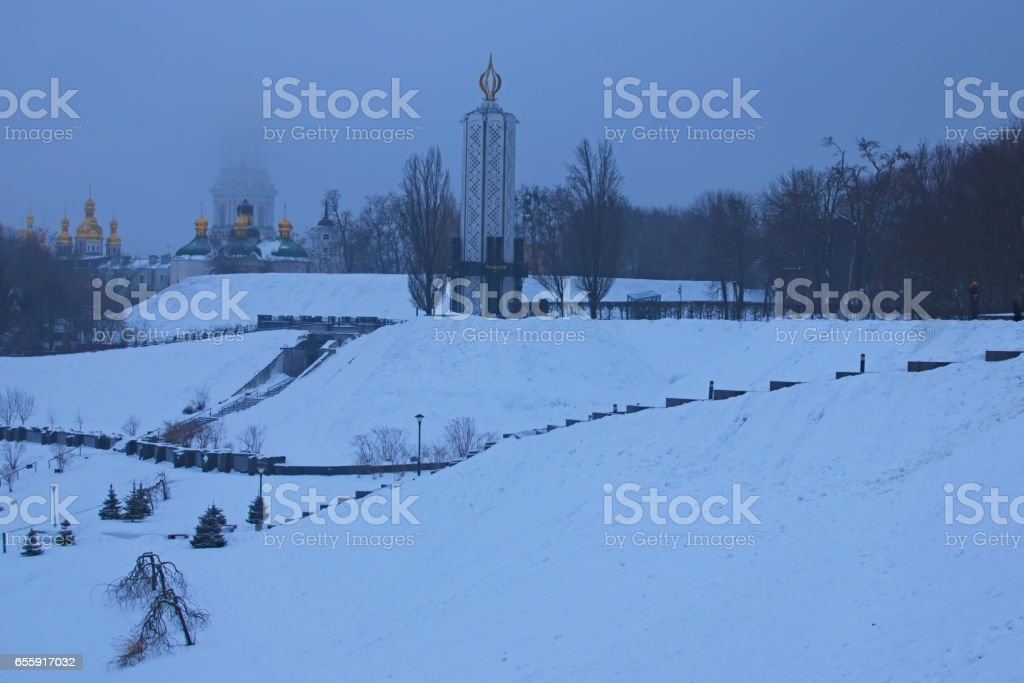 Frosty winter morning in the park. National Museum 'Memorial to Holodomor victims' and top of Great Lavra Bell Tower is disappearing in the fog. Kiev. Ukraine stock photo