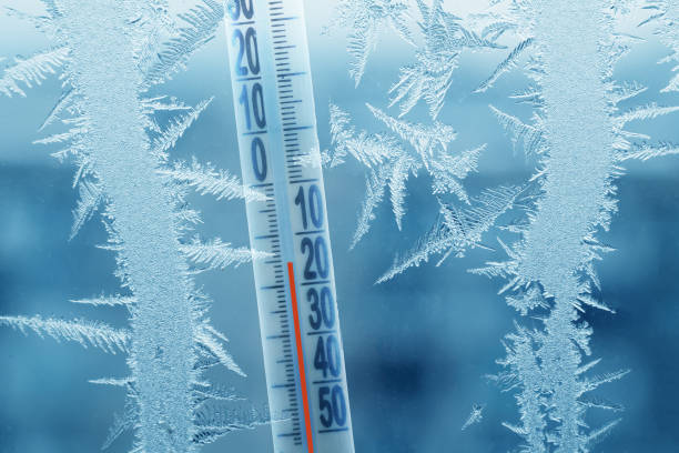 ijzig winter venster met ijs patronen en een thermometer met een temperatuur van min - koud stockfoto's en -beelden