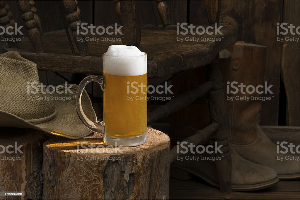 Frothing beer in clear mug w/western cowboy boots & hat royalty-free stock photo