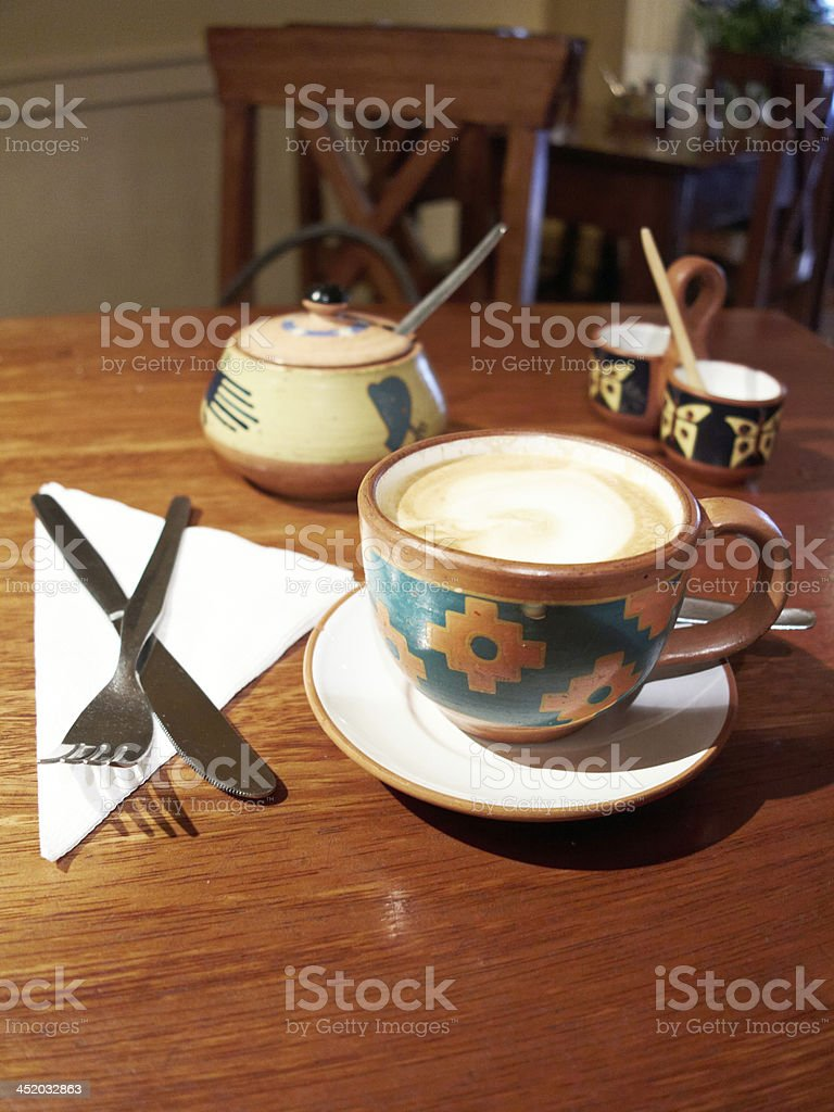 Frothy coffee served in Peruvian ethnic crockery royalty-free stock photo