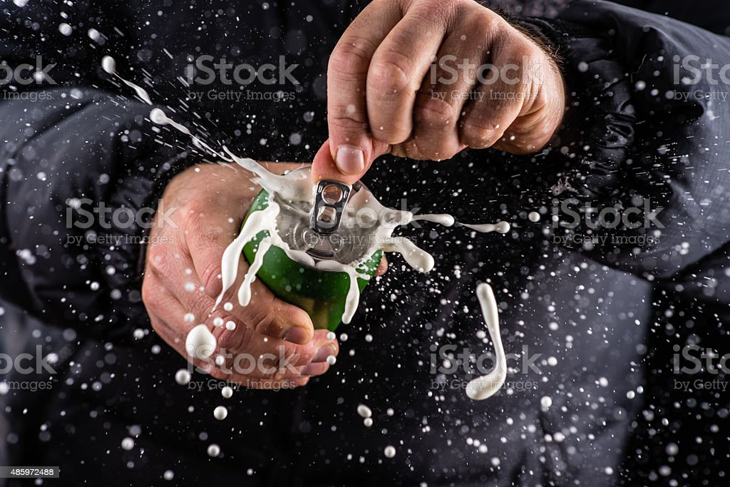 Frothy foam splashing out of a tin can stock photo
