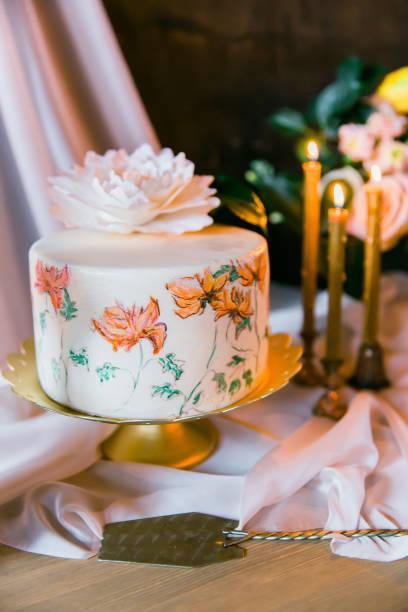 frowers, kerzen und hochzeit kuchen gemalt. still-leben - orange hochzeitstorten stock-fotos und bilder