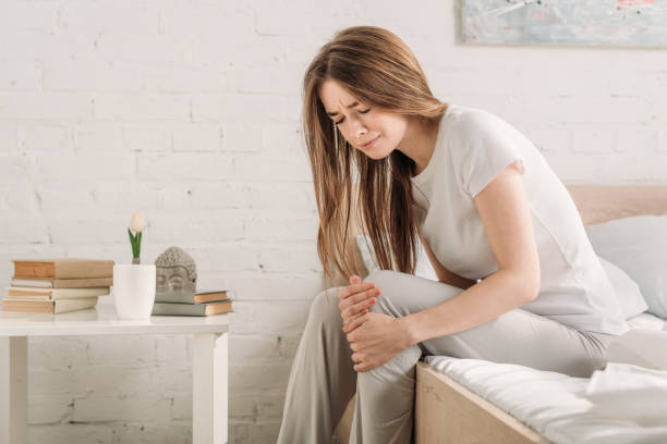 frowned girl sitting on bed near bedside table and suffering from knee pain stock photo