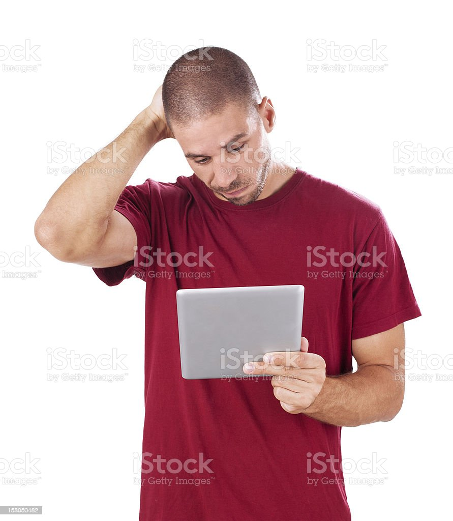 Frowned man confusedly looking at tablet PC royalty-free stock photo