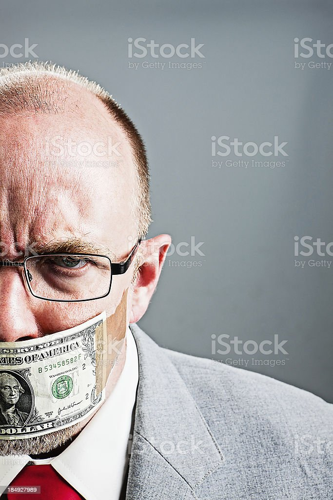 Frowning mature man gagged with dollar bill glares in frustration stock photo
