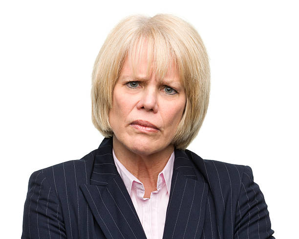 frowning mature woman looking at camera - frowning stock photos and pictures