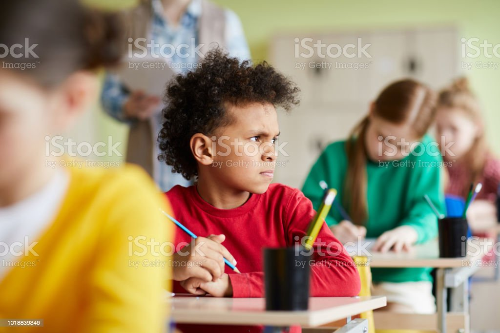 Frowning pensive African schoolboy at class Frowning pensive African schoolboy with curly hair sitting at desk and thinking about test task while looking away at class Boys Stock Photo