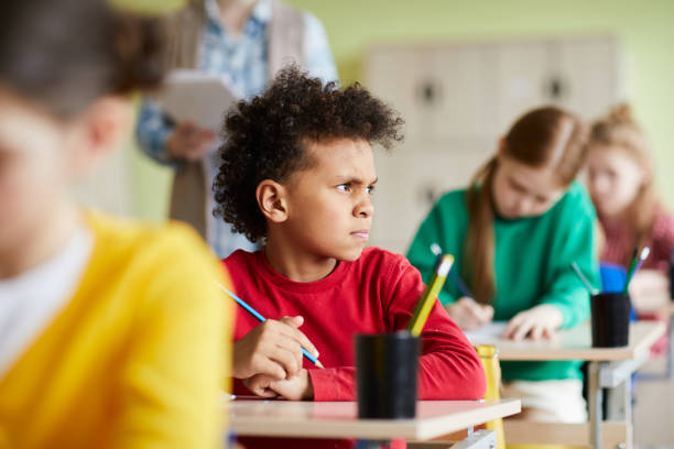 Frowning pensive African schoolboy at class Frowning pensive African schoolboy with curly hair sitting at desk and thinking about test task while looking away at class mischief stock pictures, royalty-free photos & images