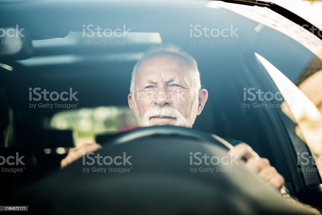 Frowning senior man driving a car and making effort to see the road.