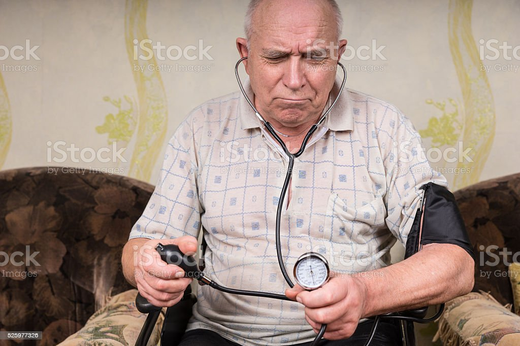 Frowning senior man monitoring his blood pressure stock photo