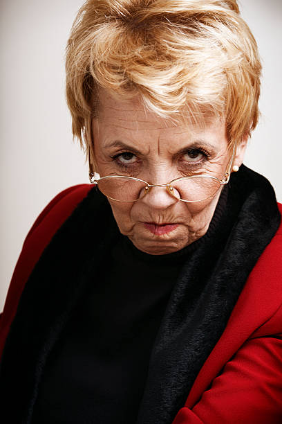 Frowning senior woman Angry senior woman looking at camera. cruel stock pictures, royalty-free photos & images