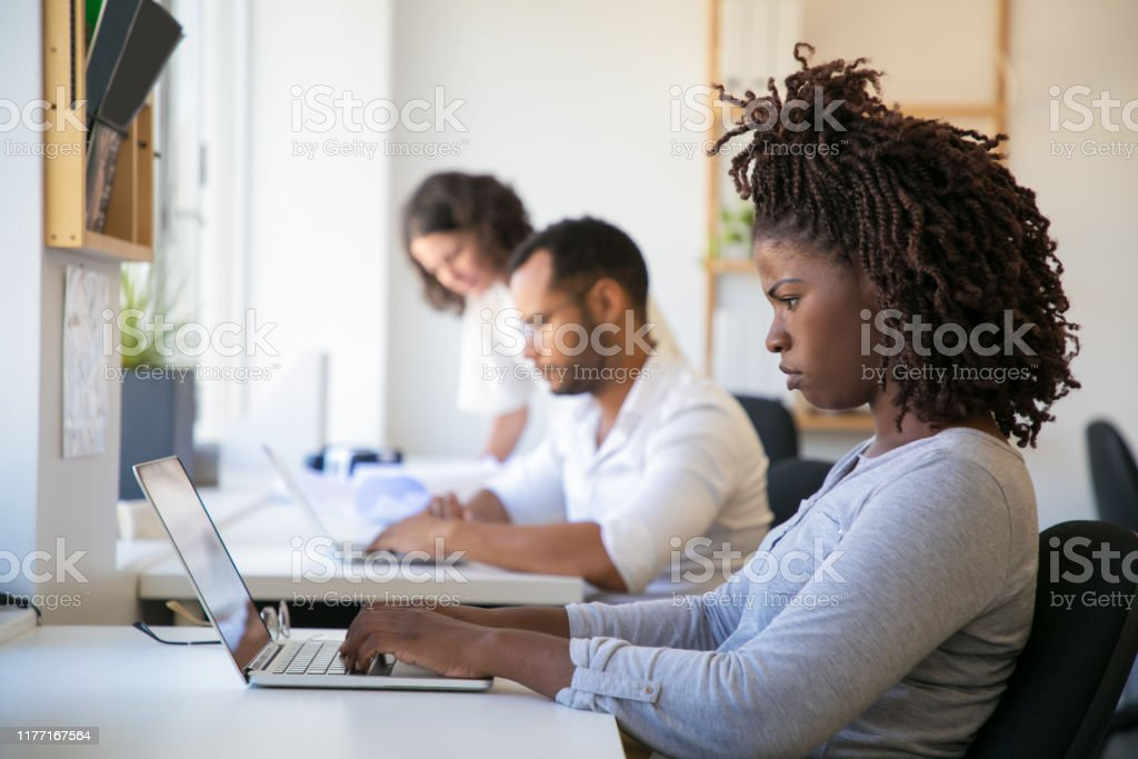 Frowning young female employee working on project Frowning young female employee working on project in office. Man and women in casual sitting and standing at table and using laptops. Diverse staff concept Adult Stock Photo