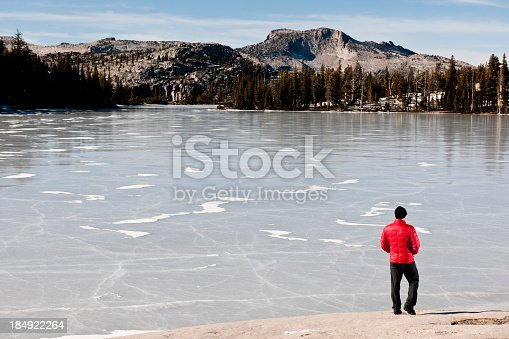 A hiker looking over a frozen lake