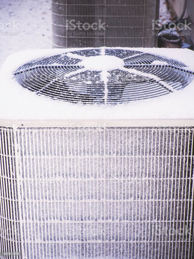 Frozen air conditioning unit covered in snow stock photo