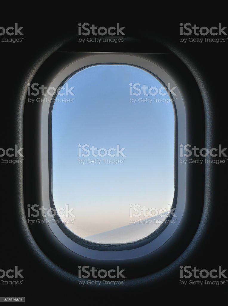 Frozen airplane window view from inside, seeing blue and pink sky and part of aircraft's wing. Inside the plane is dark, but outside is bright during day time. stock photo