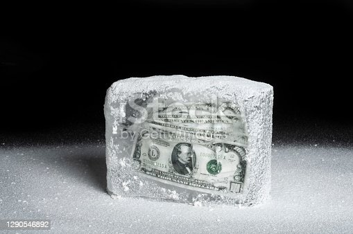 An ice block covered with snow. A fan of $1000 bills are contained inside the block representing frozen assets