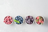 Frozen berries in small bowls on a concrete background from copies of space.