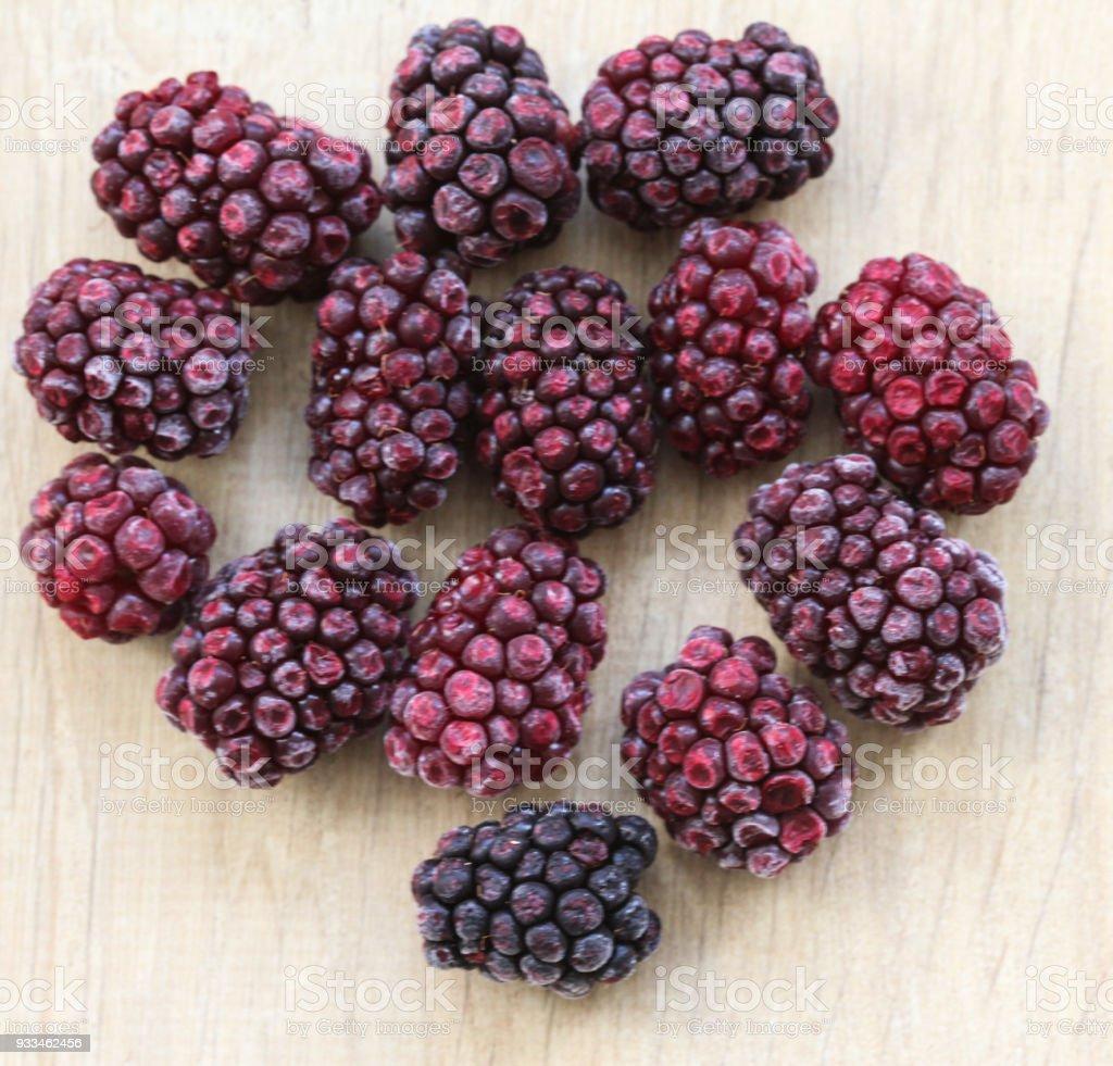 Frozen blackberries on wooden background in kitchen stock photo