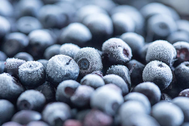frozen blueberries background - frozen berries stock photos and pictures