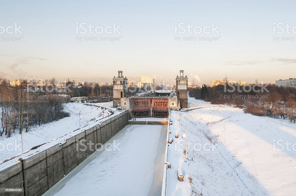 Frozen canal with shipping lock against skyline background at sunset stock photo