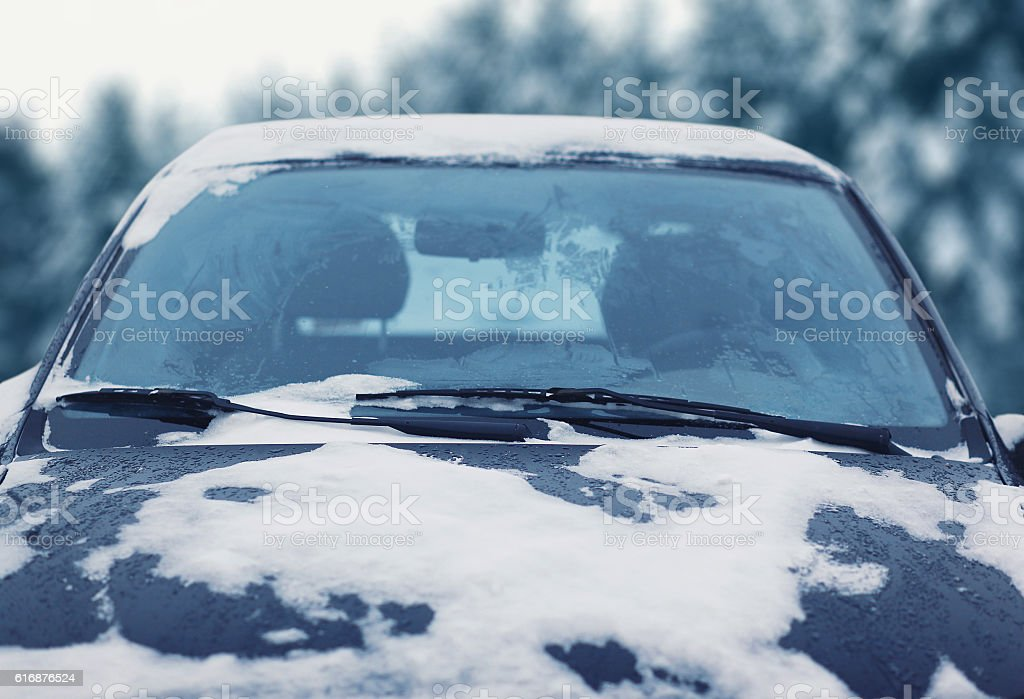 Frozen car covered snow in winter day, view windshield hood stock photo