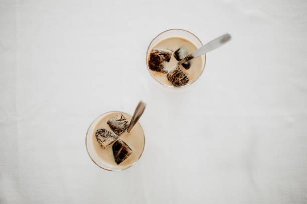 gefrorenen kaffee-eiswürfel in ein glas gegossen mit milch zu einer erfrischenden sommer iced kaffee trinken. weißer hintergrund, ansicht von oben, isoliert, raum kopieren. - hausgemachter eiskaffee stock-fotos und bilder