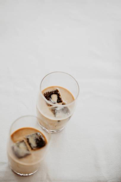 gefrorenen kaffee-eiswürfel in ein glas gegossen mit milch zu einer erfrischenden sommer iced kaffee trinken. weißer hintergrund, isoliert, raum zu kopieren. - hausgemachter eiskaffee stock-fotos und bilder