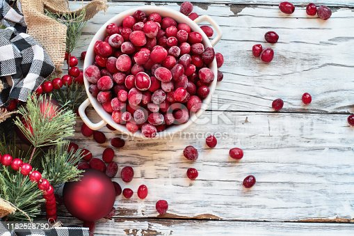 Frozen cranberries in a bowl over a white wood table background with Christmas decorations. Top view.
