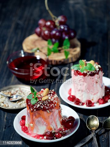 Homemade frozen dessert made of vegan soy cream cheese, red berries and honey, served with chopped almonds and cranberry syrup