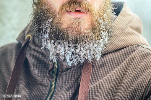 Frozen beard with hanging icicles close up background. Frosty harsh winter concept.