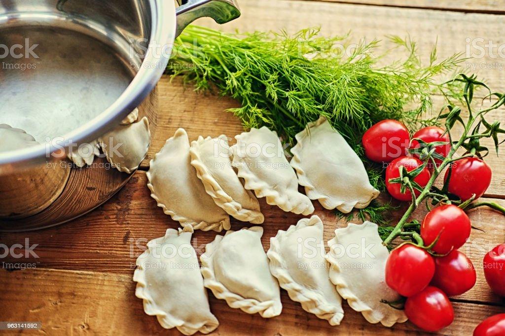Frysta dumplings med körsbärstomater och persilja. - Royaltyfri Deg Bildbanksbilder