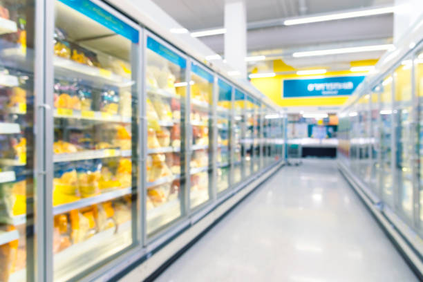Frozen food freezers and shelves in the supermarket. Frozen food freezers and shelves in the supermarket. Picture in defocused background. Picture with grain and color from film simulation filter. aisle stock pictures, royalty-free photos & images