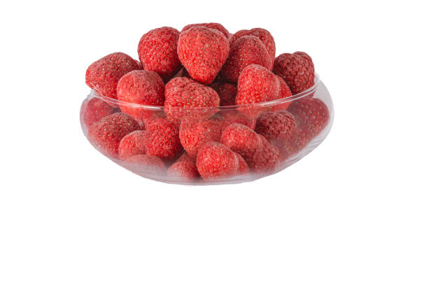 Frozen fruit on a white background and in a glass bowl stock photo