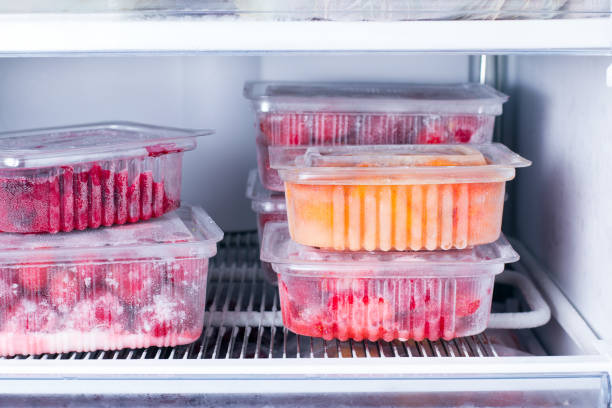frozen fruits and berries in a container in the freezer - frozen berries stock photos and pictures