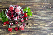 Frozen fruits. Frozen fruit mixture of currants, cherries and strawberries. Vitamin Blend. On a dark background. Copy space.