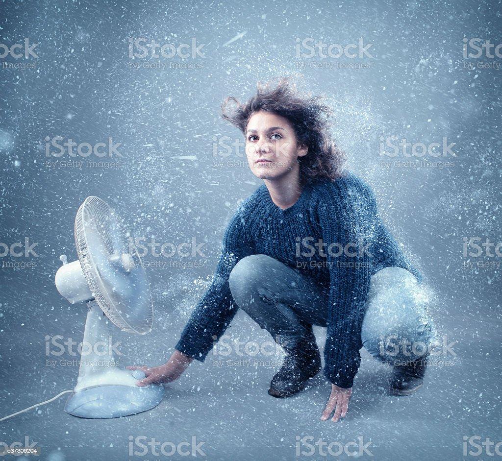 Frozen girl beside a powerful fan stock photo