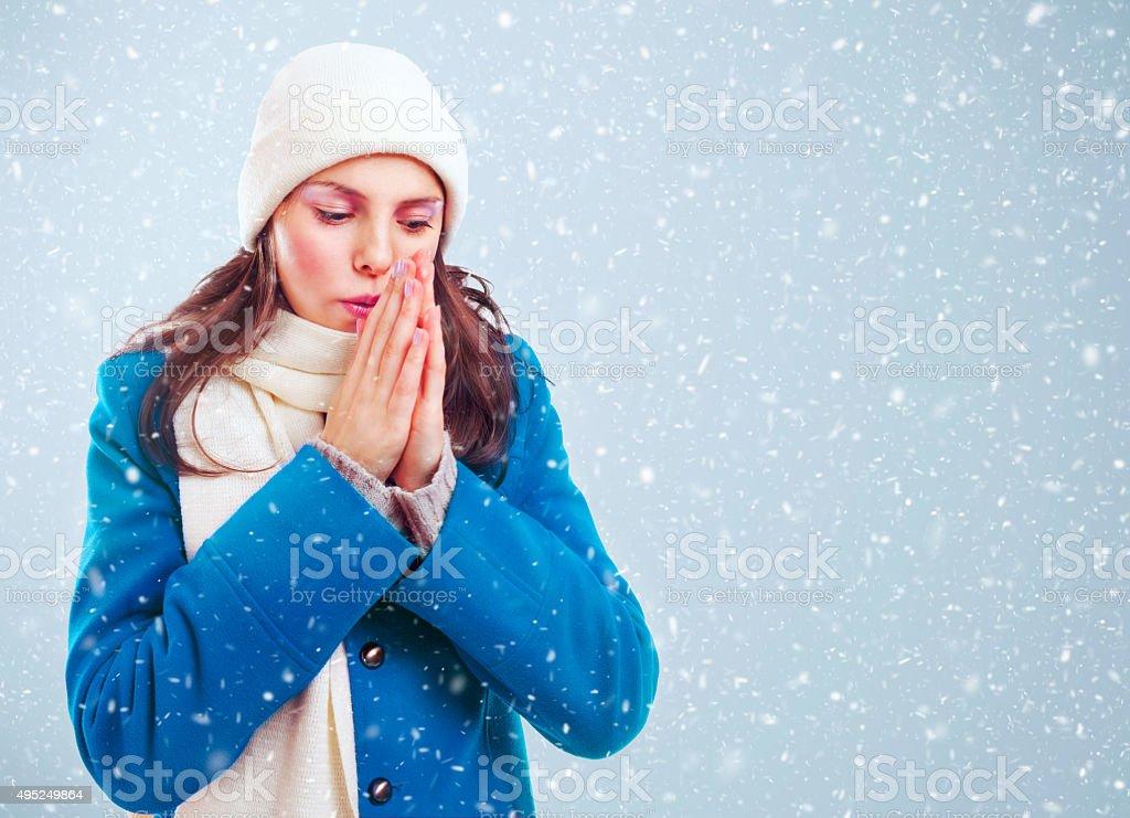 Frozen girl heats hands among winter snowstorm stock photo