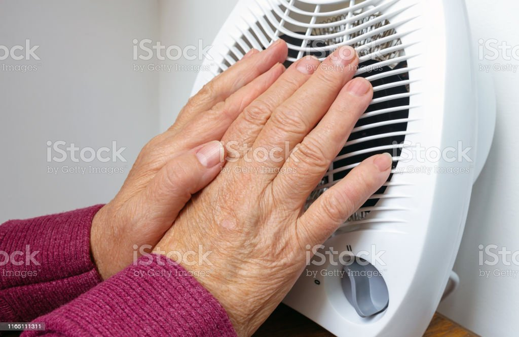 A frozen hands of an elderly woman near electric heater on a cold winter day. Conceptual image of heating in winter. Selective focus, close-up. A frozen hands of an elderly woman near electric heater on a cold winter day. Conceptual image of heating in winter. Selective focus, close-up. Adult Stock Photo