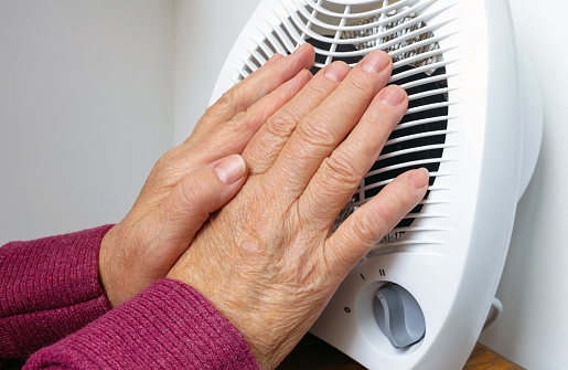 A Frozen Hands Of An Elderly Woman Near Electric Heater On A Cold Winter Day Conceptual Image Of Heating In Winter Selective Focus Closeup Stock Photo - Download Image Now