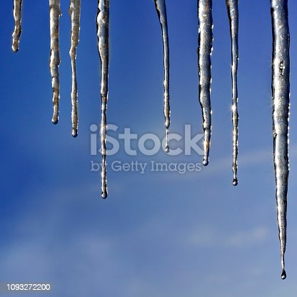 Frozen Icicles Isolated on Blue Sky Background. Square frame