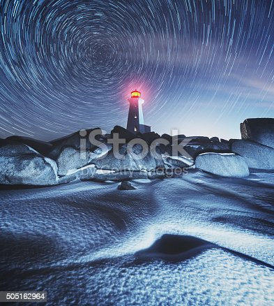 Earth's axis is revealed high above the frozen landscape surrounding Peggy's Cove Lighthouse. Long exposure with light painting.