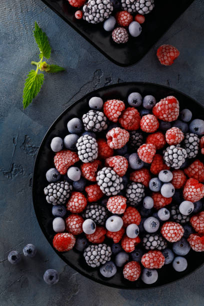 frozen juicy and ripe berries of blueberries, blackberries and raspberries, top view - frozen berries stock photos and pictures