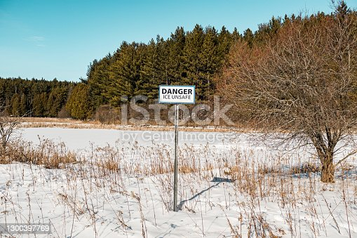 Frozen lake sign on the shore of frozen lake in the winter.