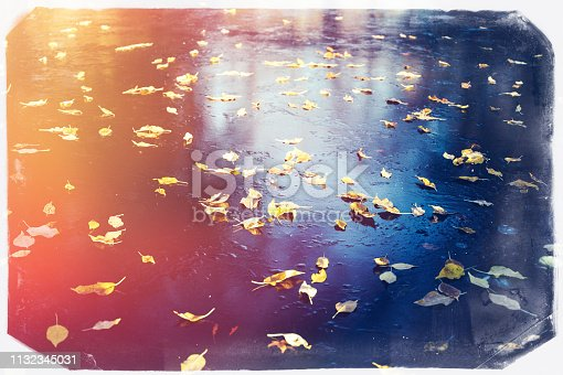 Frozen lake surface with yellow leaves in the blue ice with vintage film effect frame